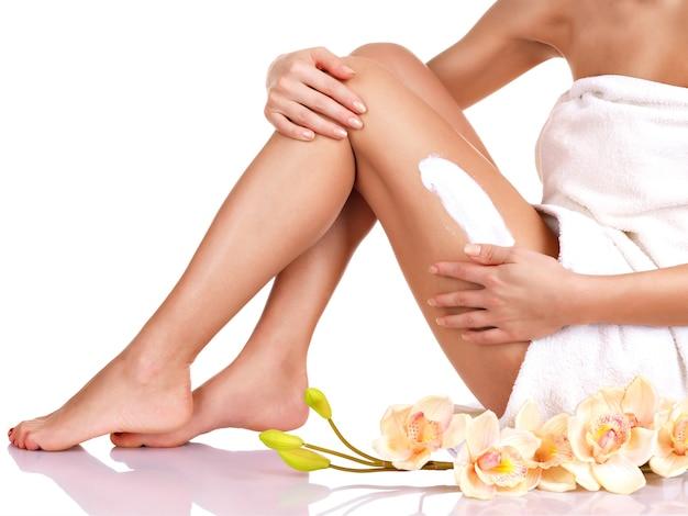Donna con un bel corpo utilizzando una crema sulla gamba su uno sfondo bianco Foto Gratuite