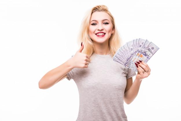 Donna con bel viso e corpo tenendo il ventaglio fatto di banconote sul muro bianco Foto Gratuite