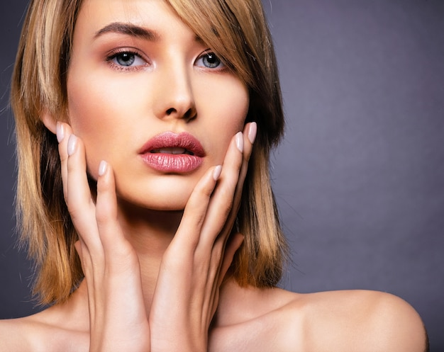 Woman with beauty face and clean skin.  sexy blonde woman.  attractive blond model with blue eyes. fashion model with a smokey makeup. closeup portrait of a pretty woman. creative short hairstyle. Free Photo