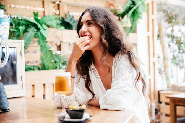 Женщина с пивом, питающимся маслинами Бесплатные Фотографии