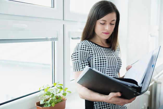 Woman with big folder posing in office Free Photo