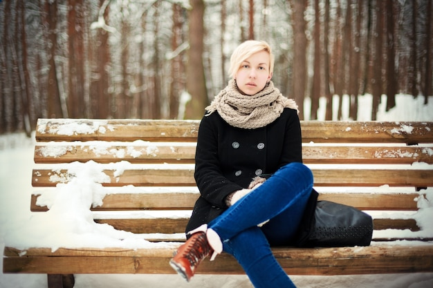 Woman with black coat sitting on a bench with snow Free Photo
