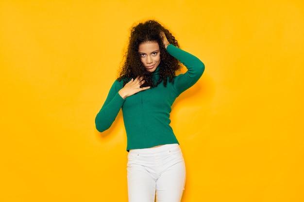 黒い巻き毛グラマーグリーンブラウスを持つ女性その孤立した黄色の背景に湖 Premium写真