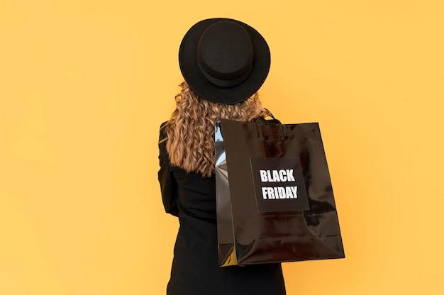 Donna con borsa venerdì nero da dietro il colpo Foto Gratuite
