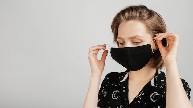 黒のシャツとマスクを持つ女性 無料写真