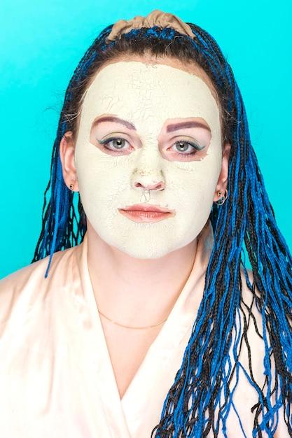 녹색 점토로 만든 냉동 마스크에 파란색 아프리카 머리 띠 얼굴을 가진 여자. 프리미엄 사진
