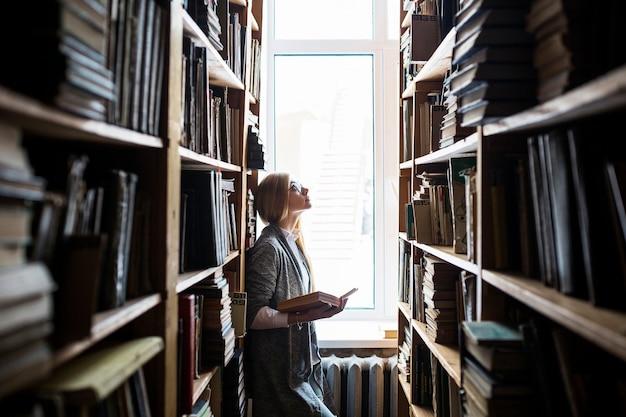 Женщина с книгой, глядя на книжные полки Premium Фотографии