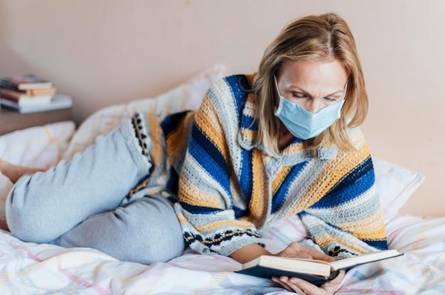 Donna con libro e mascherina medica in quarantena a casa Foto Gratuite