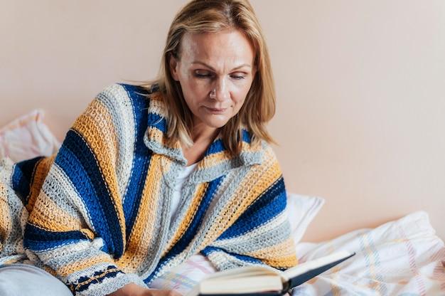 Donna con libro in quarantena Foto Gratuite