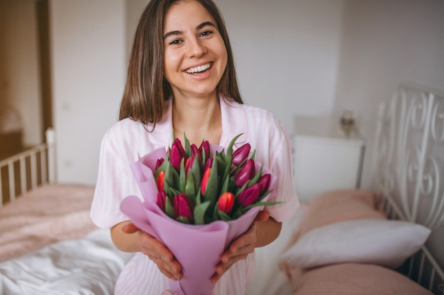 Woman with bouquet of flowers in bedroom Free Photo