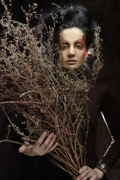 Woman with bright make up with dry branches Premium Photo