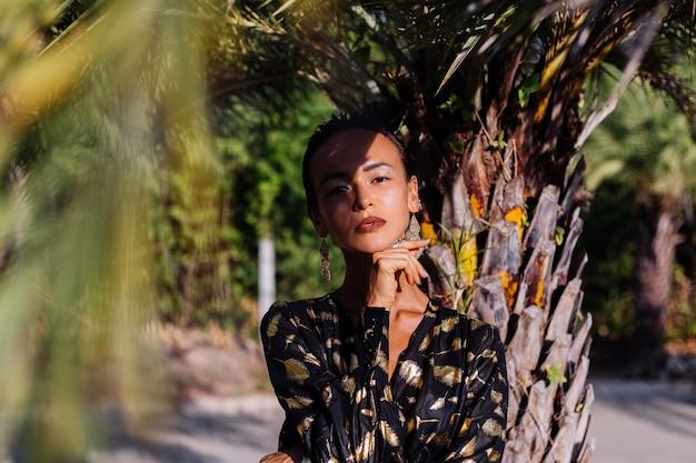 Donna con trucco in bronzo in abito nero dorato vicino a una palma Foto Gratuite