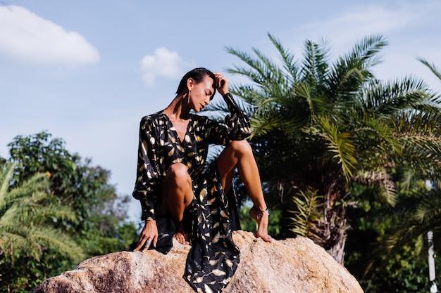 Donna con trucco in bronzo in abito nero dorato seduto sulla pietra Foto Gratuite