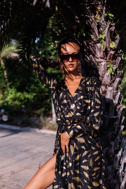 熱帯の風景の中で黒の金色のドレスとサングラスを身に着けているブロンズメイクの女性 無料写真