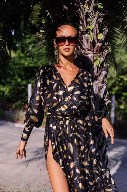 Donna con trucco di bronzo che indossa abito nero dorato e occhiali da sole nel paesaggio tropicale Foto Gratuite
