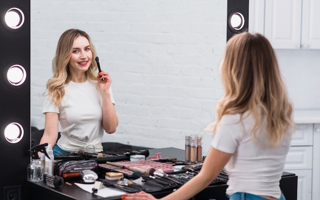Woman with brush for makeup standing at mirror Free Photo