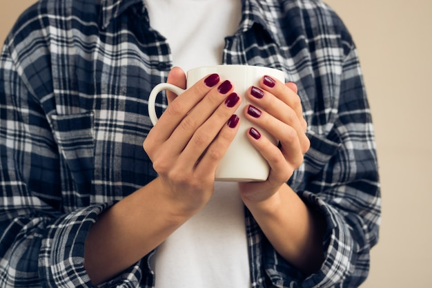 Woman with a burgundy manicure in plaid shirt holding white cup Premium Photo