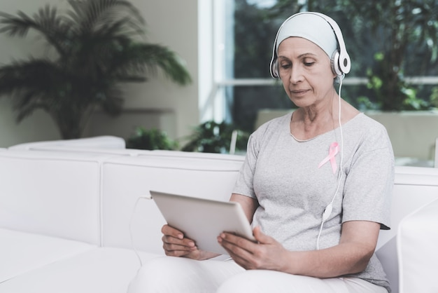 Woman with cancer is sitting on sofa in a modern clinic. Premium Photo
