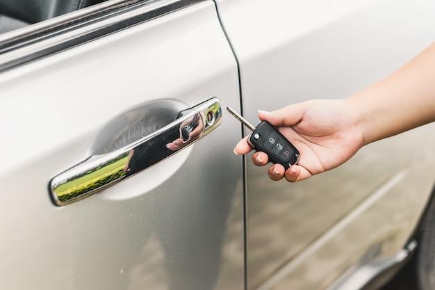 Woman with car key near the door Free Photo