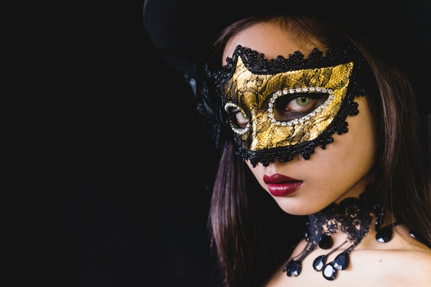 Woman with a carnival mask on a dark background Free Photo