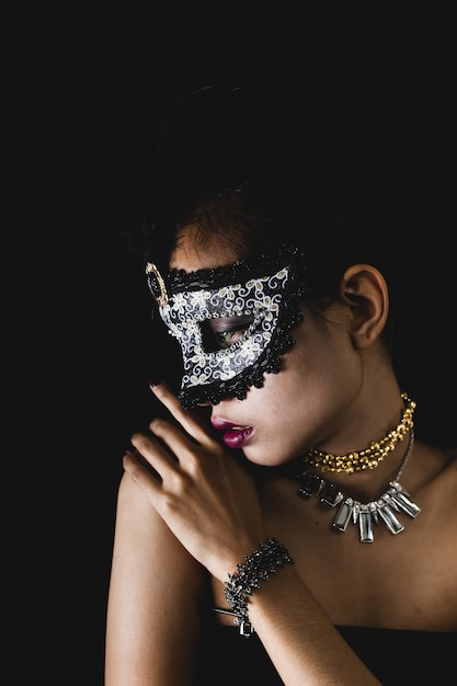 950a95451424 Woman with a carnival mask on a dark background Photo | Free Download
