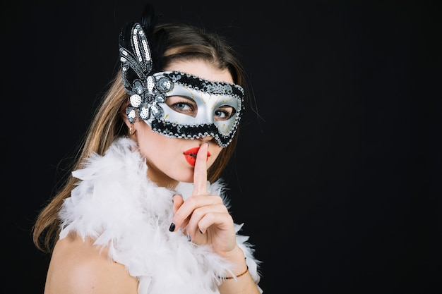 d98813478b7c Woman with a carnival mask making silence gesture on black background Free  Photo