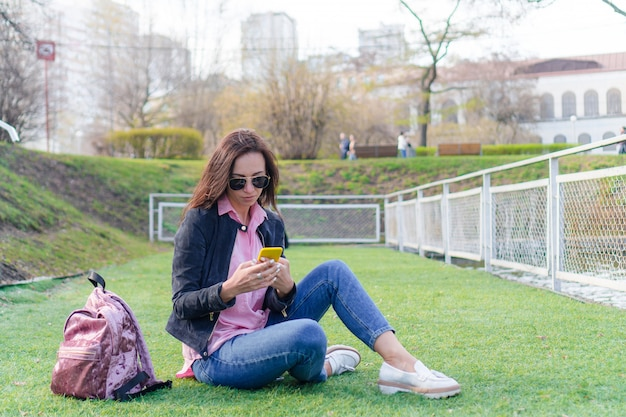 Woman with cellphone outdoors on the street. woman using mobile smartphone. Premium Photo