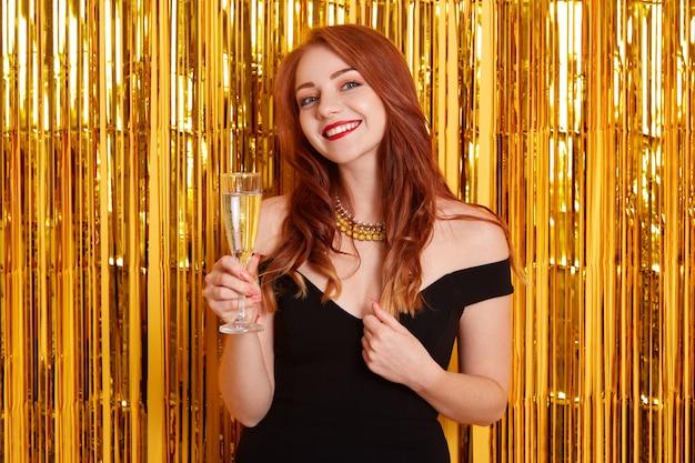 新年を祝う魅力的な笑顔の女性、グラスワインを持って、エレガントな黒のドレスを着て、金色の見掛け倒しで黄色の壁にポーズをとる。 無料写真