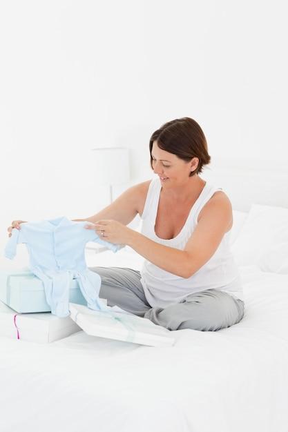 Женщина с детской одеждой Premium Фотографии