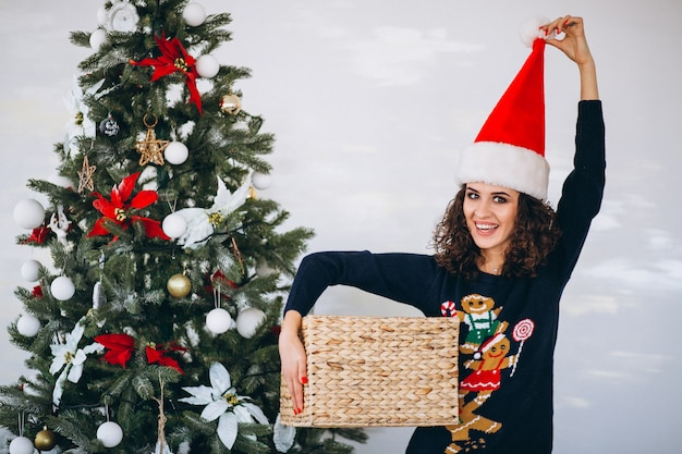 Woman with christmas present by christmas tree Free Photo