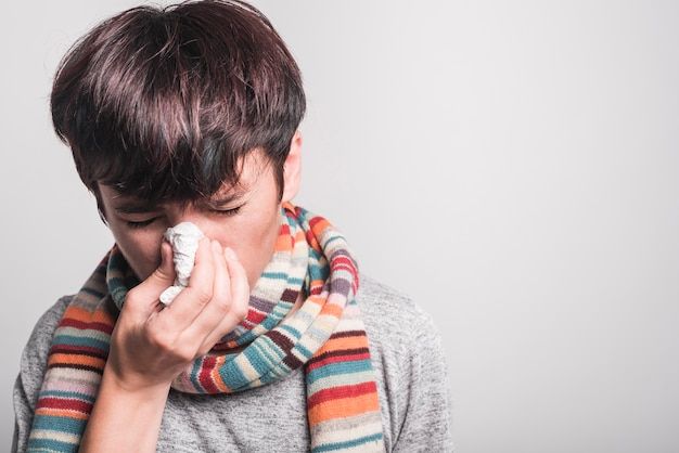 Woman with closed eyes blowing her nose into tissue paper against gray background Free Photo