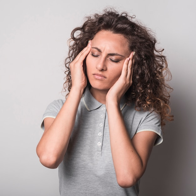 Woman with closed eyes having headache against gray background Free Photo