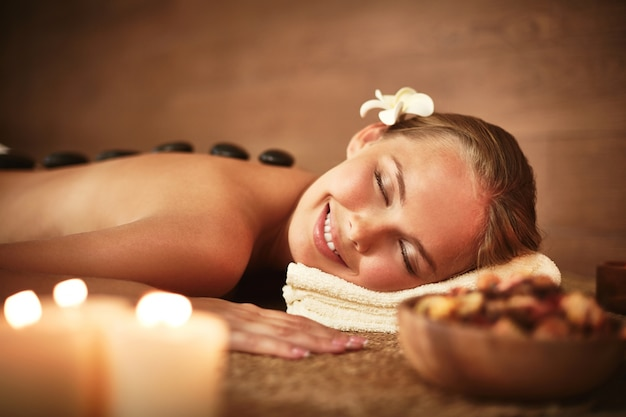 Woman with closed eyes receiving hot stone massage Free Photo