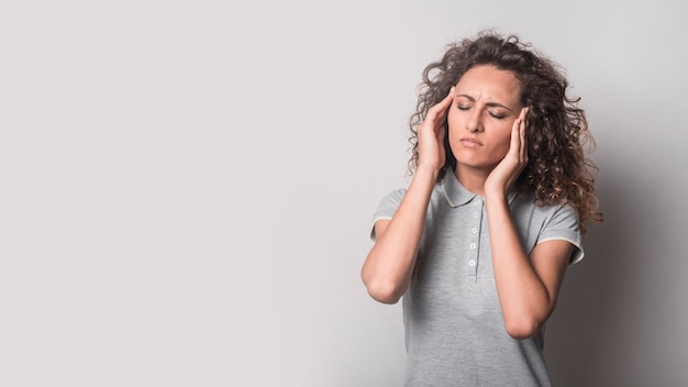 Woman with closed eyes suffering from headache against gray background Free Photo