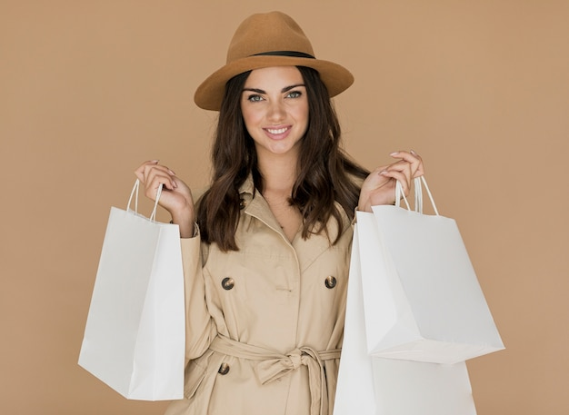 Woman with coat and hat on brown background Free Photo