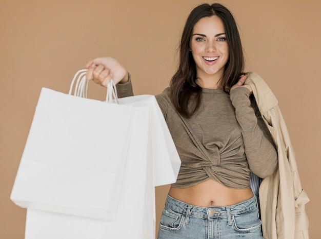 Woman with coat on shoulder and white shopping bags Free Photo
