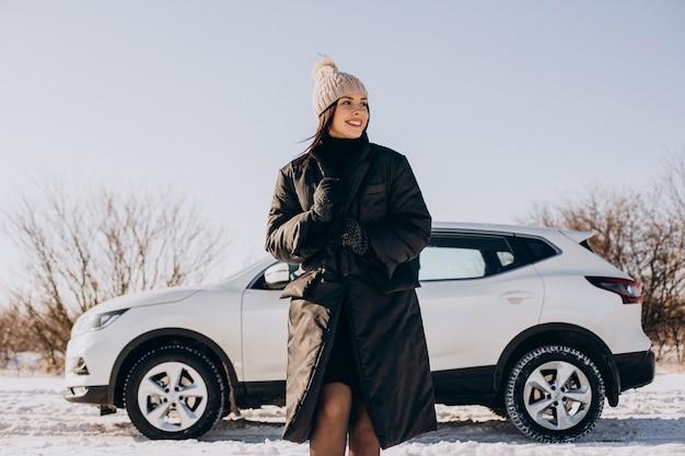 冬のフィールドで車のそばに立っているコーヒーとコーヒーの女性 無料写真