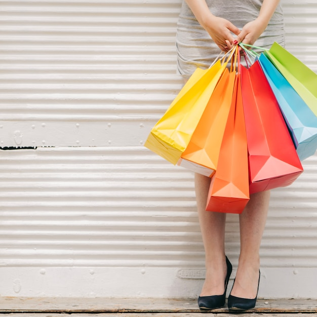 Woman with colorful bags at wall Free Photo