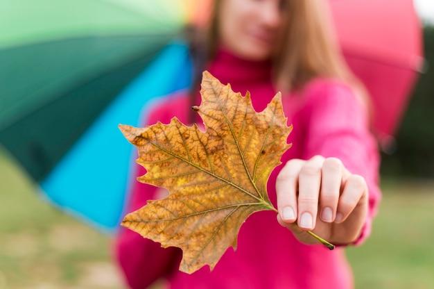 Женщина с красочным зонтиком держит осенний лист Бесплатные Фотографии