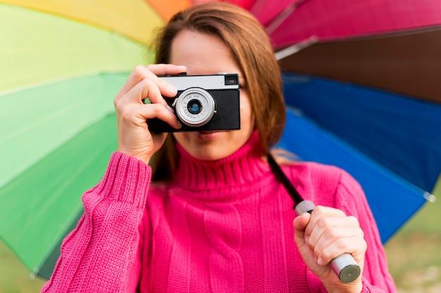Женщина с красочными зонтик, принимая фотографию с ее камерой Бесплатные Фотографии