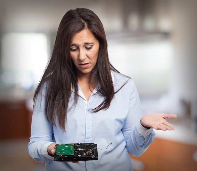 Woman with confused face looking at a hard disk Free Photo
