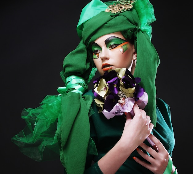 Woman with creative make up holding a bouquet Premium Photo
