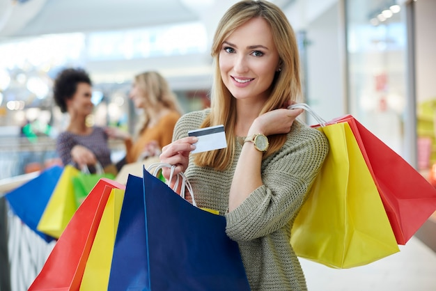 Woman with credit card and full shopping bags Free Photo