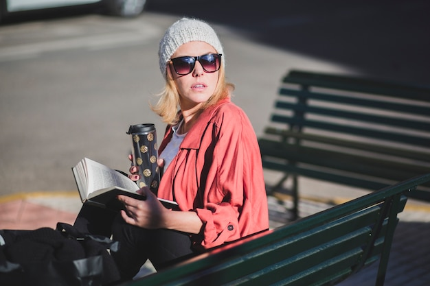 Woman with cup and book looking away Free Photo