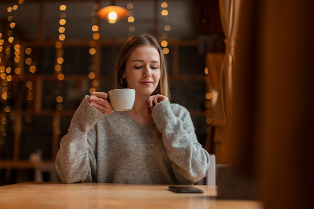 Woman with cup of coffee looking at mobile Free Photo
