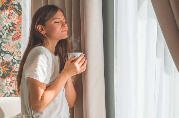 Woman with cup of hot drink by the window. looking at window and drink tea. good morning with tea. autumn winter time Premium Photo
