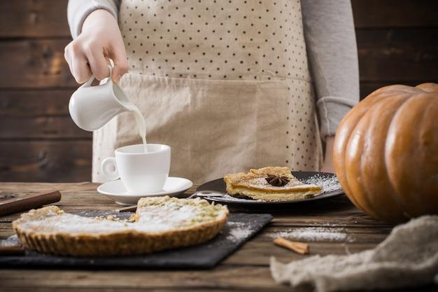 Женщина с чашкой кофе и тыквенным пирогом Premium Фотографии
