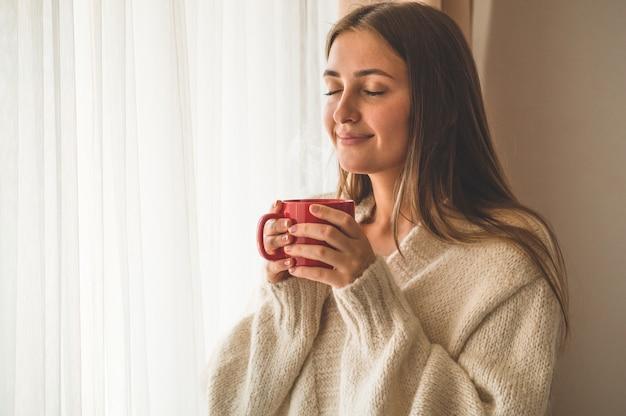 Женщина с чашкой горячего напитка у окна. доброе утро с чаем. осень зима Premium Фотографии
