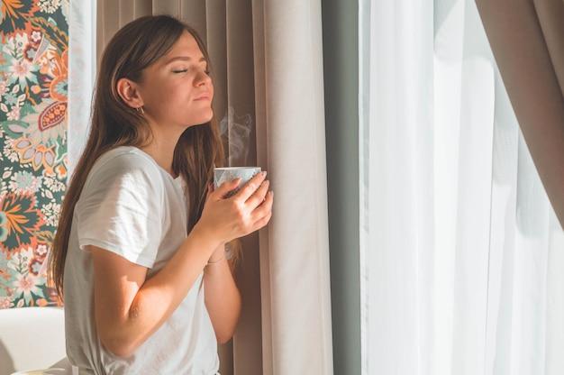 Женщина с чашкой горячего напитка у окна. глядя в окно и пью чай. доброе утро с чаем. осень зима Premium Фотографии