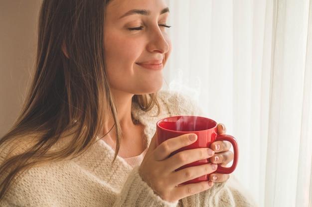 Женщина с чашкой горячего напитка у окна Premium Фотографии